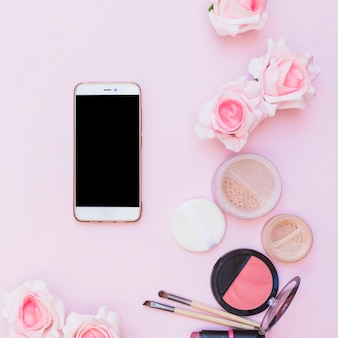 Cellphone; cosmetics products and flower on pink background on pink background