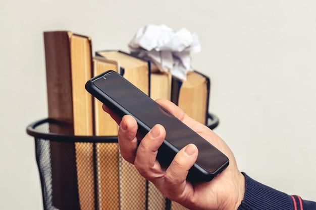古い本とゴミ箱の背景に男の手に携帯電話