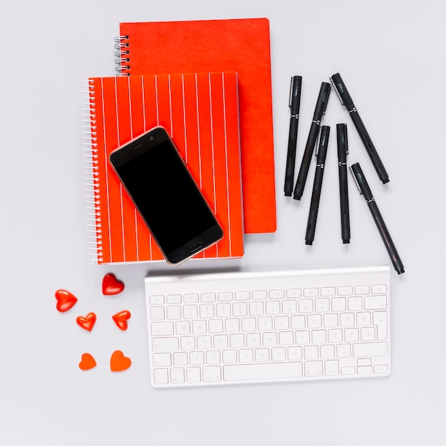 赤いカバーのスパイラルノートの携帯電話;ペンとハート型キャンディー、白いキーボード