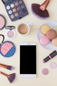 Cellphone screen; coffee with macaroons and cosmetics products on beige background