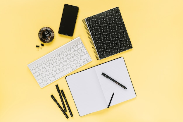 Cellphone and white keyboard with office stationery on yellow background