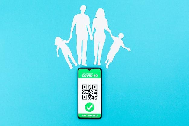 Мобильный телефон с приложением цифрового паспорта иммунитета и вырезанным из бумаги силуэтом семьи на синей стене. плоская планировка. понятие о вакцинации и новой норме. скопируйте пространство.