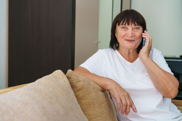 Modのソファに座っている間家族と呼んでいる陽気な白人の祖母のセルラーポートレート...
