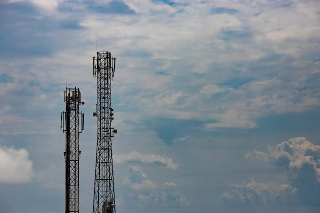 Cellular tower against a blue sky with clouds. copy space.