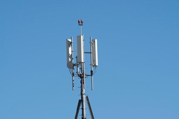 푸른 하늘이있는 건물 위에있는 셀룰러 송신기