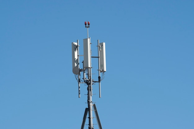 Cellular transmitters on top of building with a blue sky