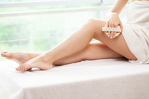 Cellulite treatment, woman arm holding dry brush to of her leg.