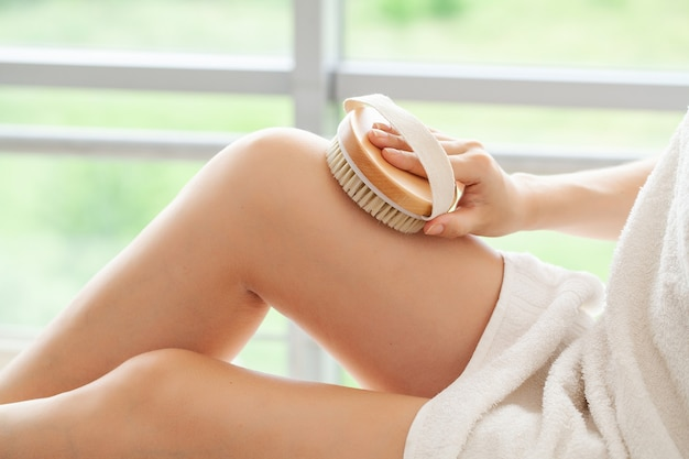 셀룰 라이트 치료, 여자 팔이 그녀의 다리에 마른 솔을 들고 있습니다.