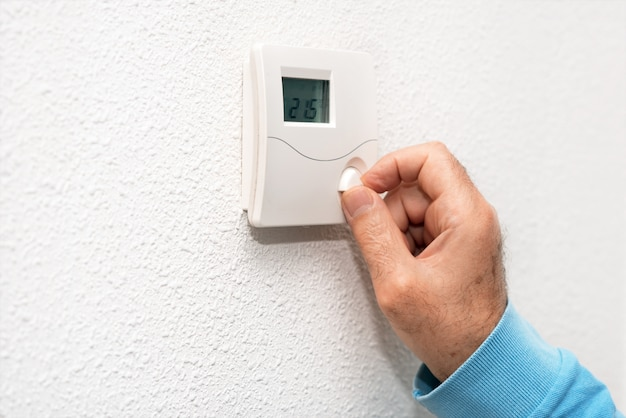 Рука регулирует термостат дома. celsius.