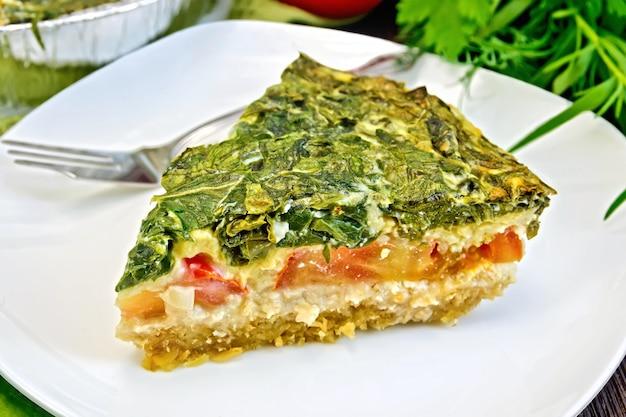 ほうれん草、トマト、オートミール、卵が入ったケルトのケーキ、白いプレートにホイル、ナプキン、木の板の背景にパセリのベーキング皿