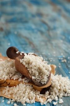 青い木製のテーブルにスプーンでケルトの灰色の海の塩