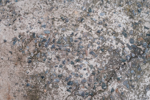 Cement floor with small stones dirty cracked old gray concrete background wall or floor