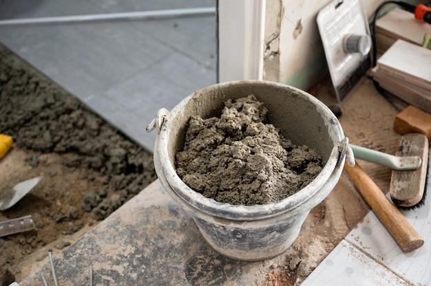 Цемент в банке с инструментами подготовка к укладке плитки