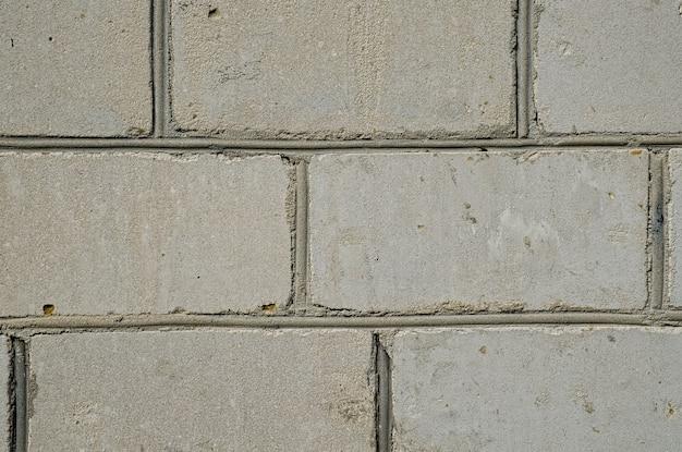 セメントまたは石灰色のレンガの壁の芸術、テクスチャ