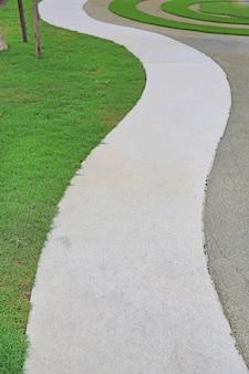 Цементная дорожка с зеленой травой рядом в саду