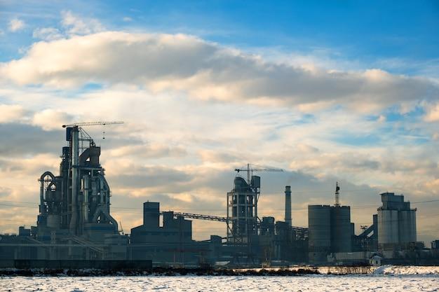 산업 생산 지역에 높은 공장 구조와 타워 크레인이 있는 시멘트 공장.