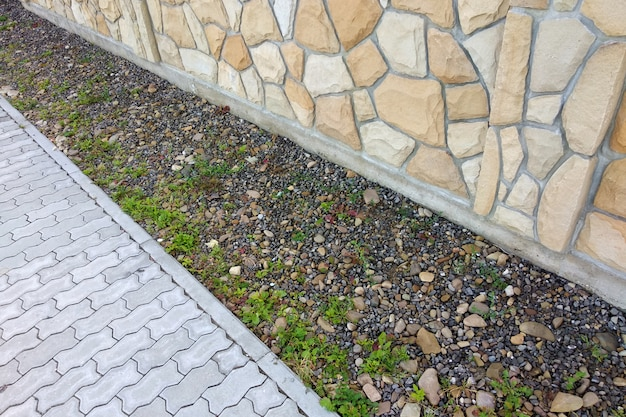 Цементная плита тротуарная возле природного камня забор или стены.