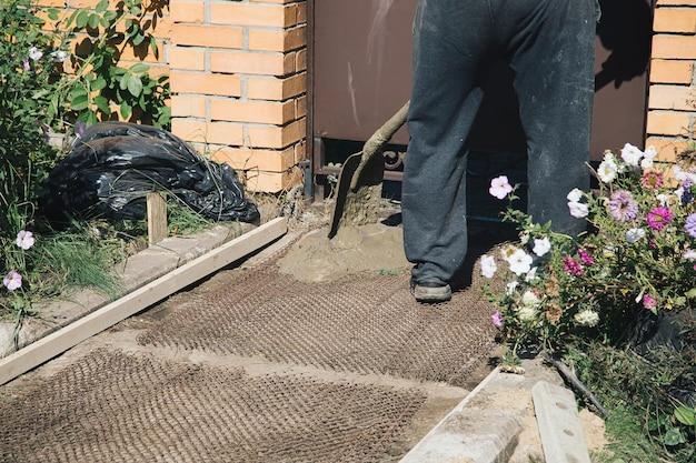 庭の金属メッシュ建設作業の上に庭の小道をセメントで固める