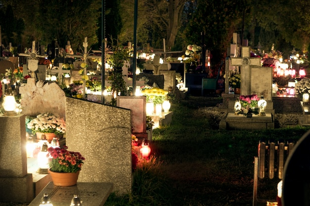 Cemetery at night, burning candles, gravestones illuminated by candlelight