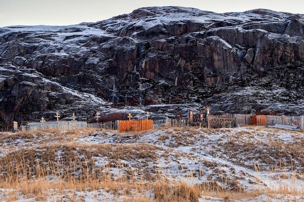Teriberka의 북극 해안 언덕 배경에 묘지