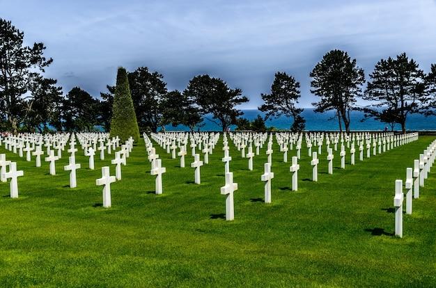 흐린 하늘 아래 푸른 나무로 둘러싸인 흰 돌 십자가가있는 묘지
