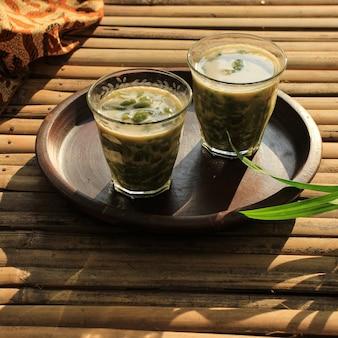 Сендол давет. перанаканский ледяной десерт из рисовой муки и зеленого желе, подается с кокосовым молоком и соусом из пальмового сахара. популярные во время рамадана