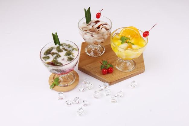 白いテーブルの上のグラスにおいしい甘いオランウータンジュース、ココナッツジュース、およびcendolインドネシアの人気のある飲み物