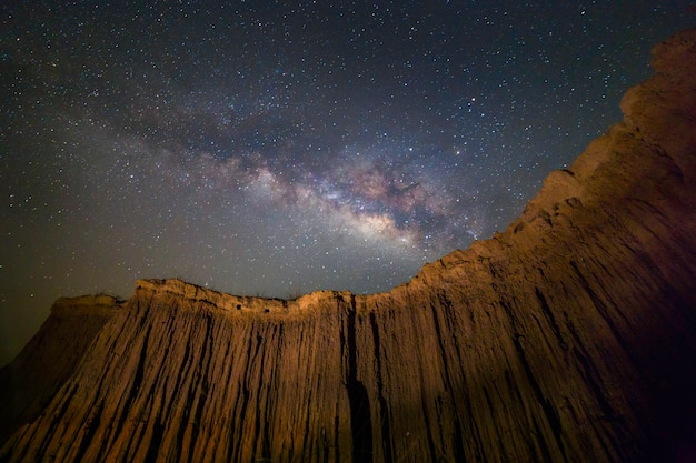 Cenic view of milky way over ancient rock in lalu, srakaew province, thailand