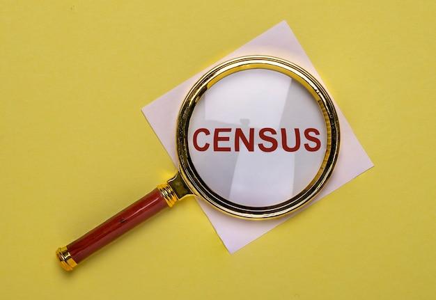 Слово переписи через лупу на желтом фоне.