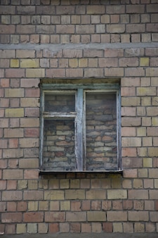In the center of the brick wall there is an old window completely covered with brickwork, walled up with bricks and cement