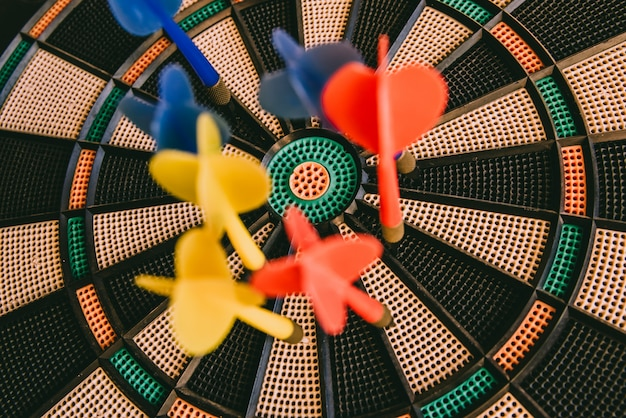 Center of a bullseye with colorful darts nailed, target concept.