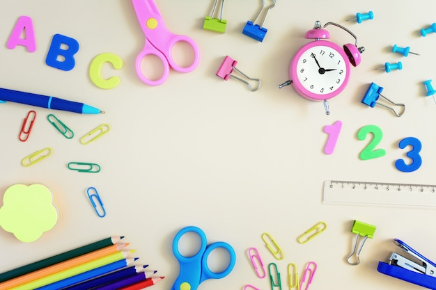 In the center of a light background with space for text, mock up. school and office supplies are spread around.