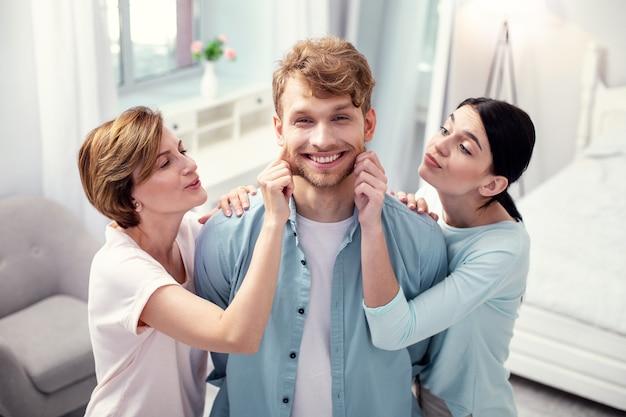 Центр внимания. довольный симпатичный мужчина, стоящий между мамой и женой, находясь в центре внимания