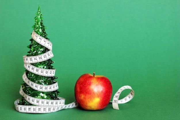 リンゴの横にある小さな緑色のおもちゃのクリスマスツリーに、長さ1センチのリボンが巻かれています。