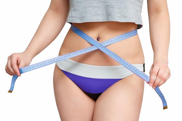 女の子のほっそりした腰に巻いたセンチメートルテープリボン。白い壁に分離