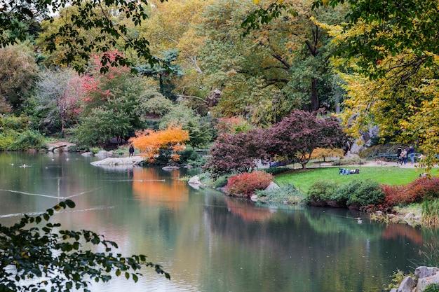 Пруд в центральном парке осенью. яркие осенние краски в парке у озера нью-йорк, сша.