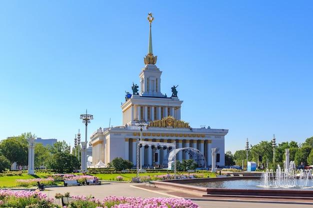 晴れた夏の朝の人々の噴水友情を背景にモスクワの国民経済(vdnh)の成果の展示会の中央パビリオン