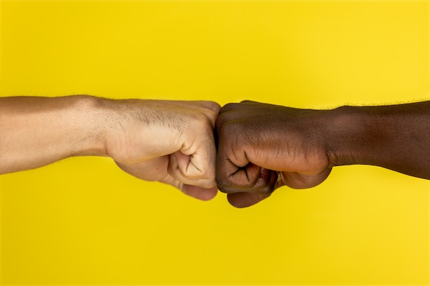 Central view of european and afroamerican hand to hand clenched into fists