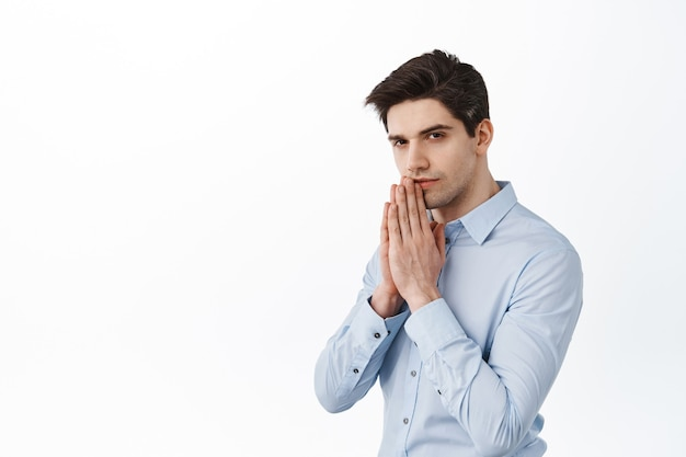 Ceo corporate man, businessman praying, holding hands in pray, looking at front with anticipation and serious face, begging, standing over white wall
