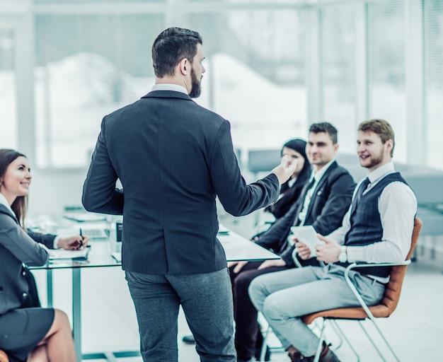 Ceo는 현대 사무실의 작업장 비즈니스 팀에서 연설합니다. 사진에 텍스트를위한 빈 공간이 있습니다.