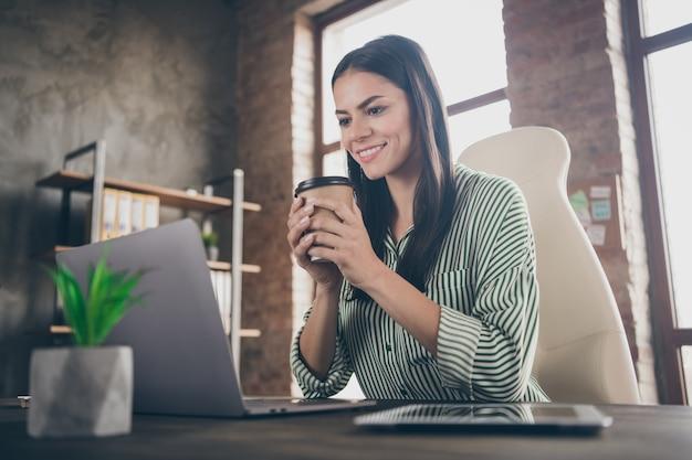 Исполнительный директор девушка-специалист сидит за столом и смотрит на экран ноутбука, держа чашку кофе в офисе