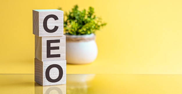 Ceo word made of wooden cubes on a yellow background with copy space, business concept