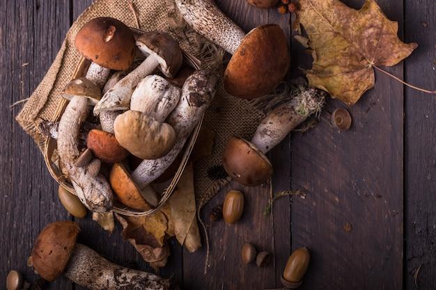 Белые грибы белые грибы на деревянных фоне. грибы подосиновика осени закрывают вверх на деревянной деревенской таблице. готовим вкусные органические грибы. изысканная еда