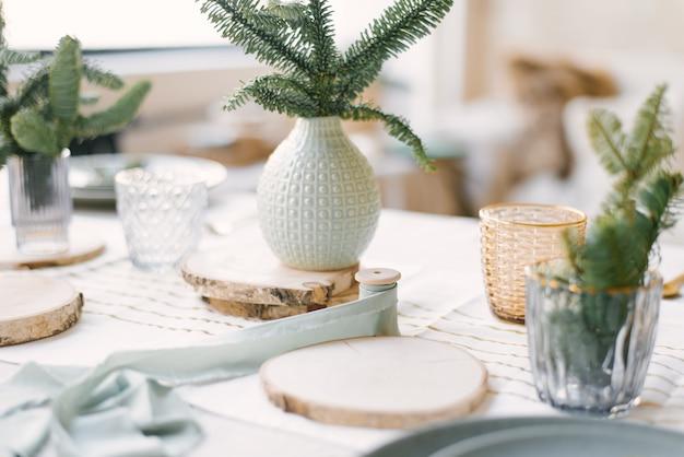 Керамические и стеклянные вазы с ветками елки