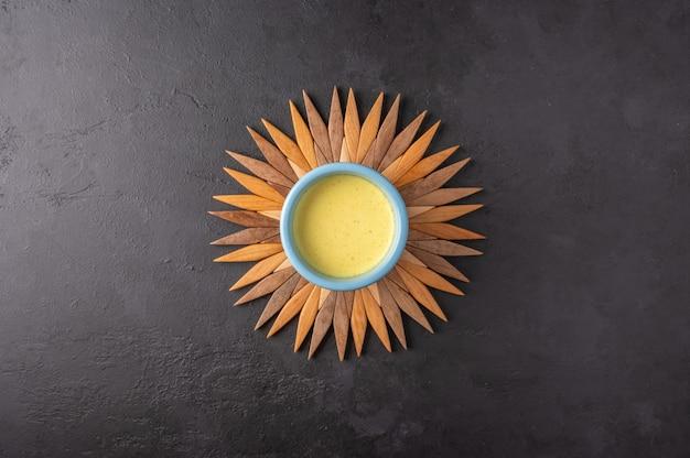 太陽の形の竹のスタンドに伝統的なインドのマサラチャイ茶とセラミックブルーカップ