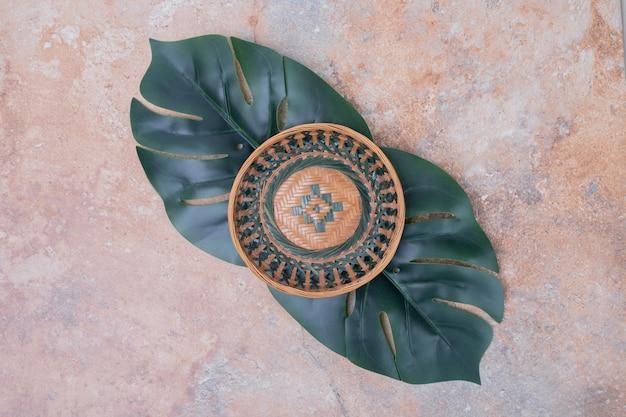 Ciotola in ceramica e foglie artificiali su superficie in marmo.