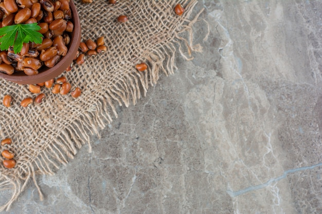 Ceramic bowl of boiled beans with burlap on marble surface.