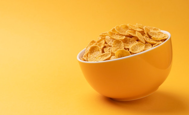 Ceramic bowl of corn flakes on yellow background with copy space