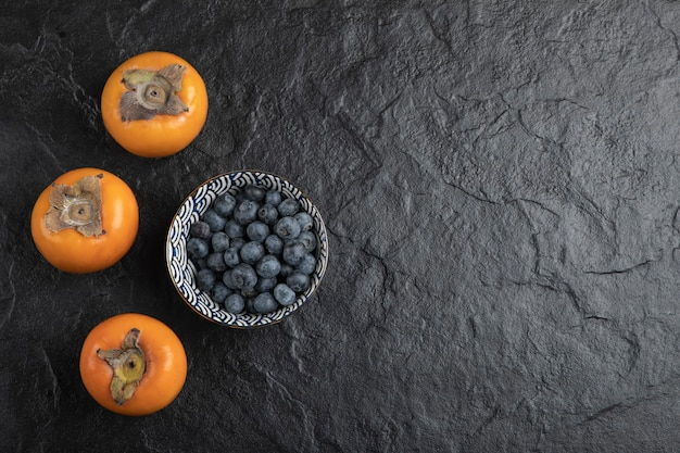 Ceramic bowl of delicious blueberries and persimmons on black surface