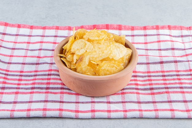 Ceramic bowl of delicious crunchy chips on stone background.